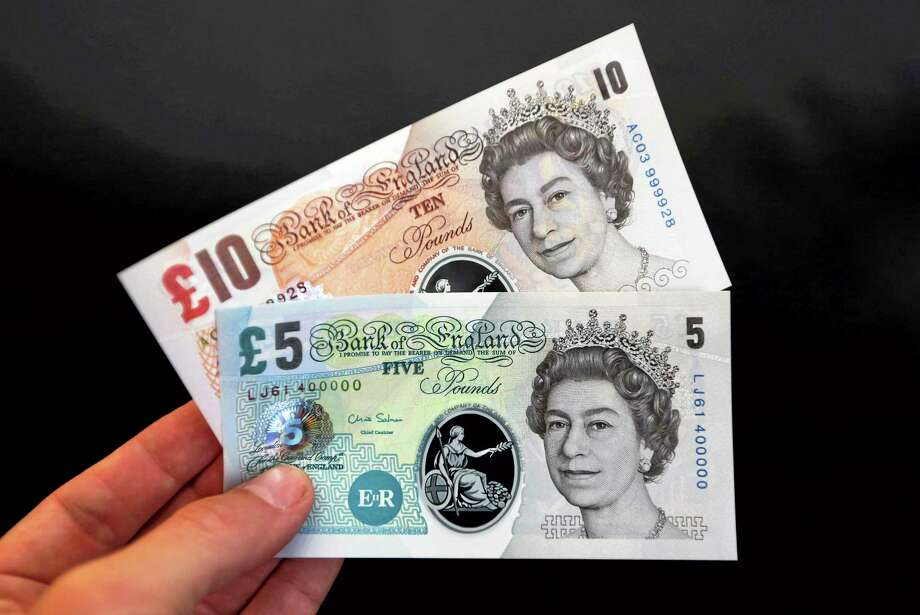"A sample the proposed new British banknotes made of a polymer, five pound and ten pound notes held for an arranged photograph during a news conference at the Bank of England in London, Tuesday, Sept. 10, 2013. Bank of England Deputy Governor Charlie Bean, said: ""Polymer banknotes are cleaner, more secure and more durable than paper money"", but the bank said Tuesday it will hold public consultations to consider the change. (AP Photo / Chris Ratcliffe) Photo: AP / POOL BLOOMBERG"