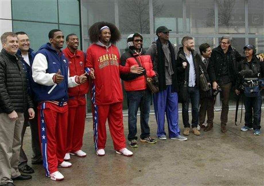 "Flamboyant former NBA star Dennis Rodman, fifth from right, poses with three members of the Harlem Globetrotters basketball team, in red jerseys, and a production crew for the media upon arrival at Pyongyang Airport, North Korea, Tuesday, Feb. 26, 2013. Rodman known as ""The Worm"" arrived in Pyongyang, becoming an unlikely ambassador for sports diplomacy at a time of heightened tensions between the U.S. and North Korea. (AP Photo/Kim Kwang Hyon) Photo: AP / AP"