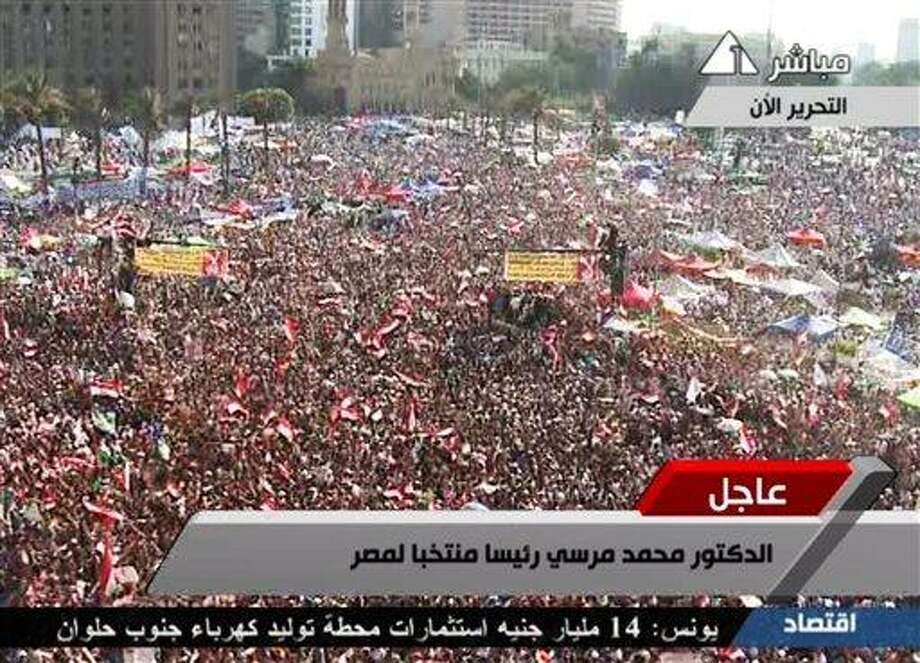 In this image taken from Egypt State TV, supporters of Muslim Brotherhood President Mohammed Morsi react Sunday to the announcement of his victory in Tahrir Square in Cairo, Egypt. Egypt's election commission has declared Morsi of the Muslim Brotherhood the winner of Egypt's first free elections by a narrow margin over Ahmed Shafiq, the last prime minister under deposed leader Hosni Mubarak. The commission said Morsi won with 51.7 percent of the vote versus 48.3 for Shafiq. Associated Press Photo: ASSOCIATED PRESS / AP2012