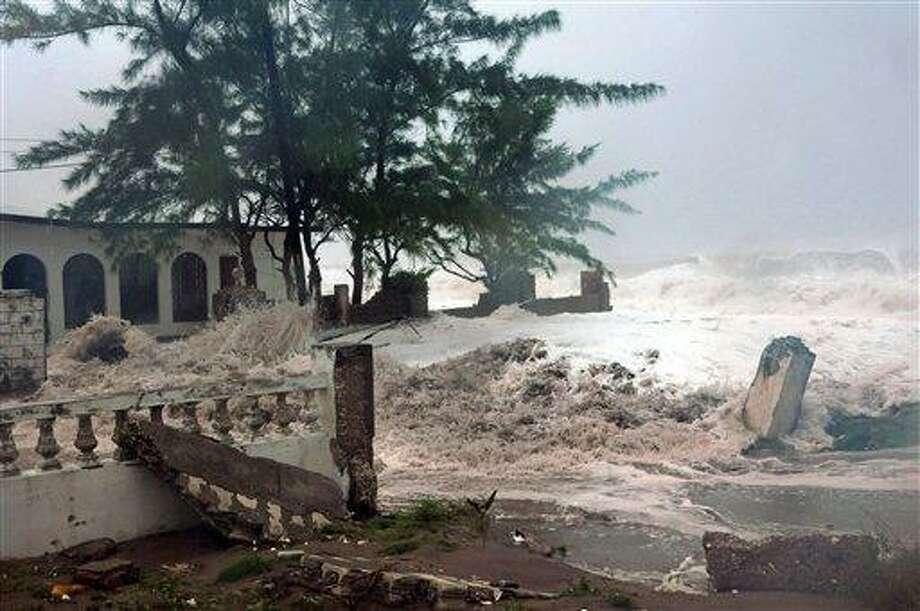 Waves, brought by Hurricane Sandy, crash on a house in the Caribbean Terrace neighborhood in eastern Kingston, Jamaica, Wednesday. AP Photo/Collin Reid Photo: AP / AP