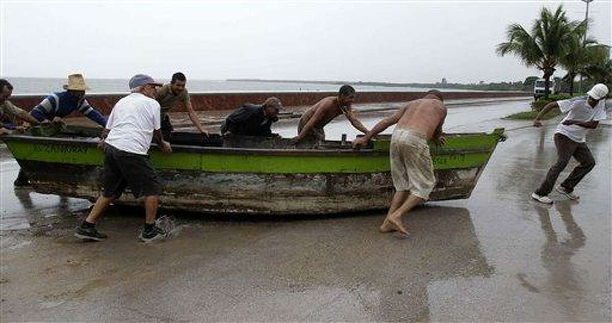 People remove a boat from the water ahead of the arrival of Hurricane Sandy in Manzanillo, Cuba, Wednesday. AP Photo/Franklin Reyes