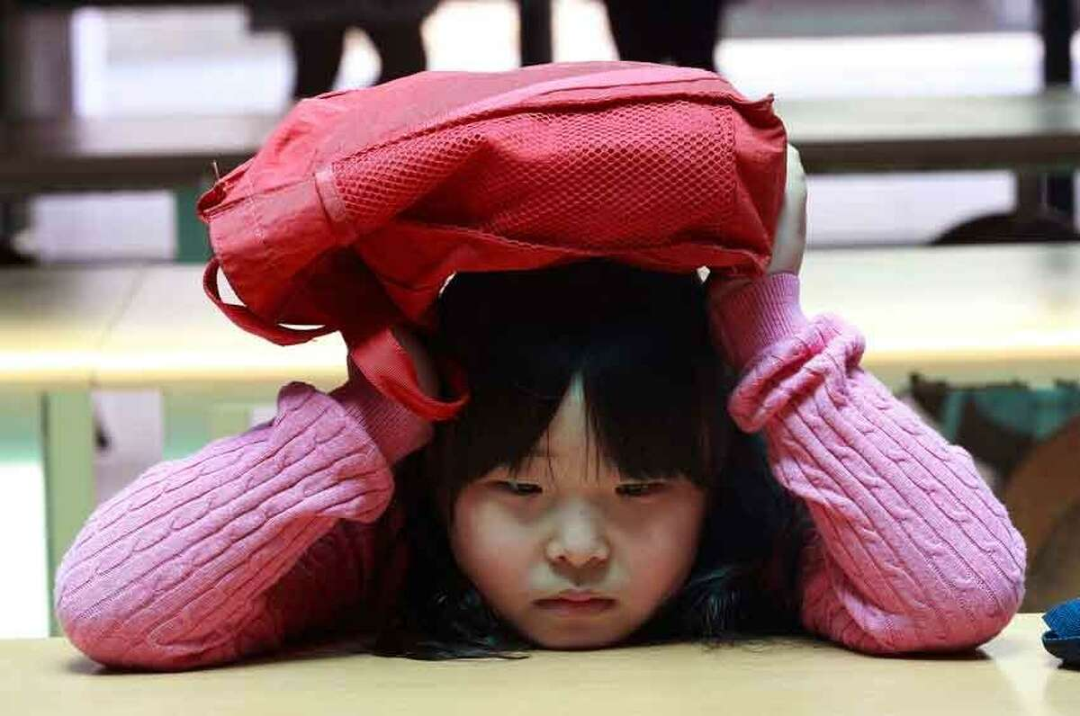 A South Korean elementary school student covers her head with a schoolbag at underground shelter after fleeing from her classroom during a drill against a possible airstrike at Sohwa elementary school in Paju near the border with North Korea, South Korea, Tuesday, May 7, 2013. Students throughout the nation took part in the drills ranging from fire to airstrike, terror attacks and earthquake as part of the annual drills called Safe Korea Exercise. (AP Photo/Ahn Young-joon)