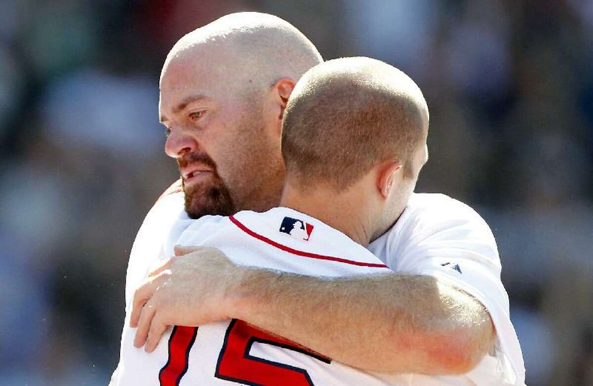 ASSOCIATED PRESS Boston Red Sox's Kevin Youkilis, left, hugs teammate Dustin Pedroia as Youklis comes off the field after hitting a triple and being replaced with a pinch runner in the seventh inning of Sunday's game against the Atlanta Braves in Boston. Youkilis has been traded to the Chicago White Sox.