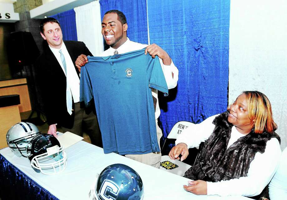 Rennick Bryan, center, holds up a UConn shirt after signing a letter of intent in 2012. Photo: Arnold Gold — Register File Photo