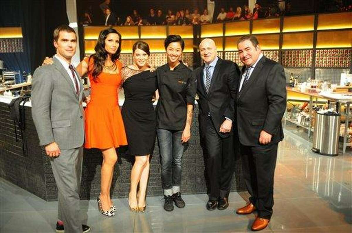"""In this publicity image provided by Bravo, """"Top Chef: Seattle"""" winner, chef Kristen Kish, third right, poses with judges, from left, Hugh Acheson, Padma Lakshmi, Gail Simmons, Tom Colicchio, and Emeril Lagasse after show's finale that aired Wednesdays, Feb. 27, 2013. The 28-year-old chef de cuisine at Boston restaurant Stir was crowned champion of the Bravo cooking competition Wednesday after facing off against Brooke Williamson, the 34-year-old co-executive chef of Los Angeles restaurants Hudson House and The Tripel. (AP Photo/Bravo, David Moir)"""