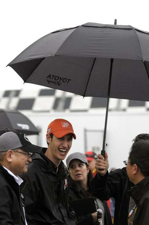 Driver Joey Logano, second from left, has a laugh while talking to spectators in the garage area prior to the NASCAR Daytona 500 Sprint Cup series auto race at Daytona International Speedway in Daytona Beach, Fla., Sunday, Feb. 26, 2012. (AP Photo/Phelan M. Ebenhack) Photo: AP / FR121174 AP