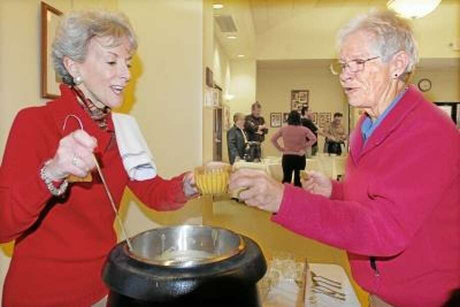 Catherine Avalone/The Middletown Press  Cynthia Clegg, president and CEO of the the Community Foundation of Middlesex County, serves up a cup of curried apple pumpkin soup made by the Ladies of Faith Lutheran Church at the annual Amazing Challenge, a soup supper at the Fox Parish Center at St. Francis of Assisi Church in Middletown Thursday evening. Amazing Grace Food Pantry served 7,617 households in 2012 and has distributed 32,448 food items in August.