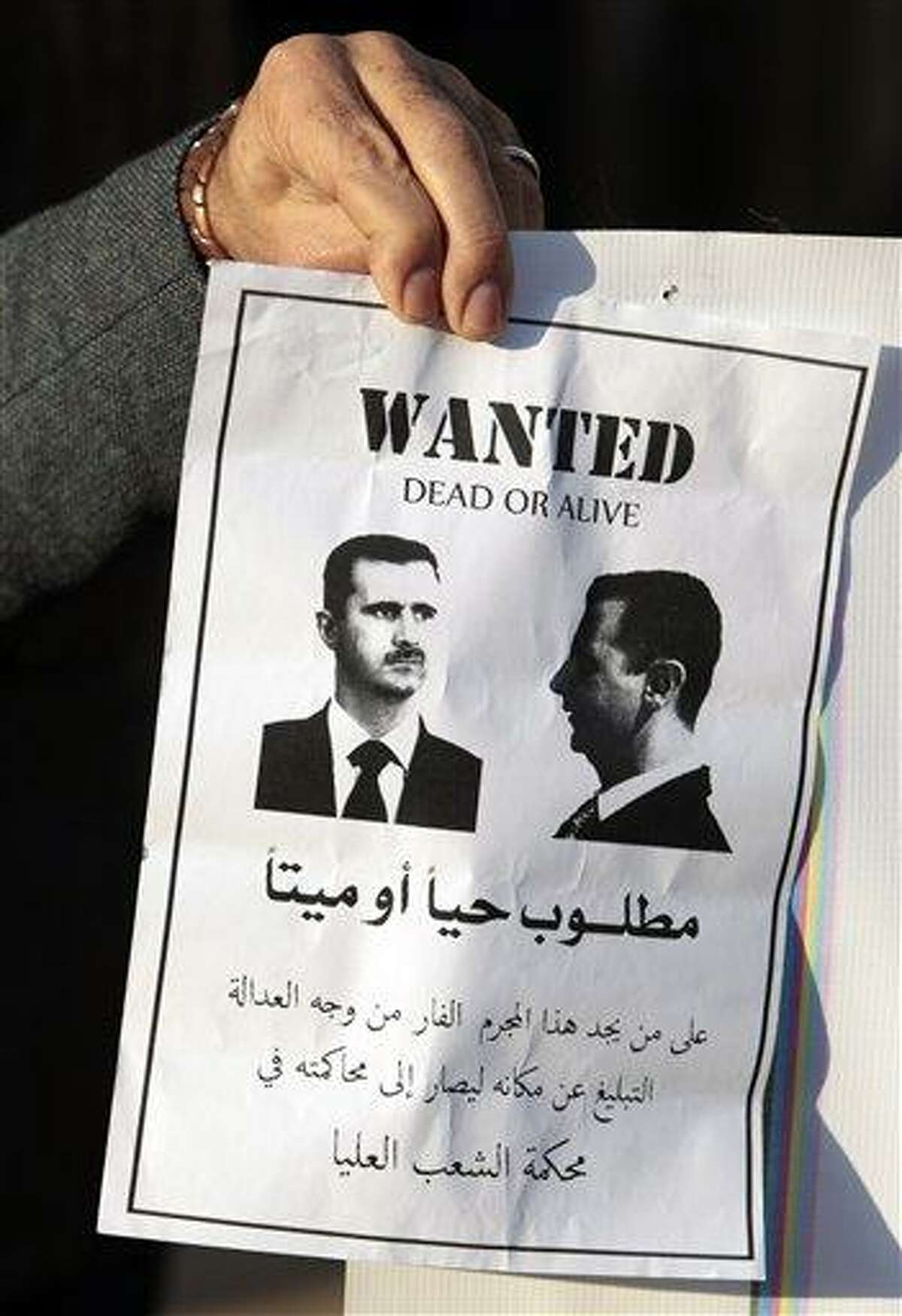 """An anti-Syrian regime protester holds a poster portraying Syrian President Bashar Assad as a """"wanted criminal,"""" with Arabic words reading: """"Whoever finds this wanted criminal, who is at large, should give information about his location in order to try him by the People's Higher Court."""" Associated Press"""