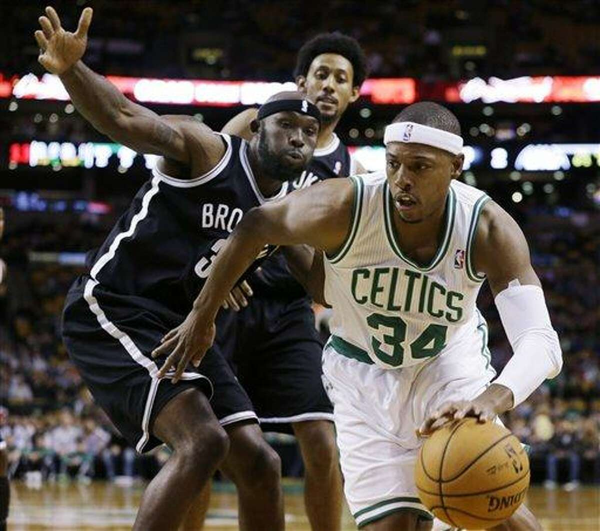 Boston Celtics' Paul Pierce (34) drives against Brooklyn Nets' Reggie Evans (30) as Josh Childress watches from behind during the first half of an NBA preseason basketball game in Boston, Tuesday Oct. 16, 2012. (AP Photo/Elise Amendola)