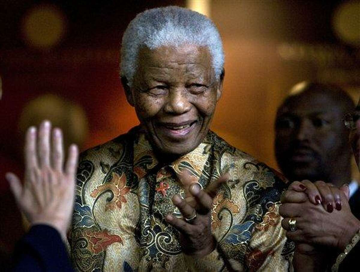 In this 2007 file photo, former South African President Nelson Mandela reacts as German Chancellor Angela Merkel, left, waves farewell after a meeting at the Nelson Mandela Foundation building in Johannesburg, South Africa. Former South African President Nelson Mandela has been hospitalized with a stomach ailment, according to a government statement issued Saturday. Associated Press