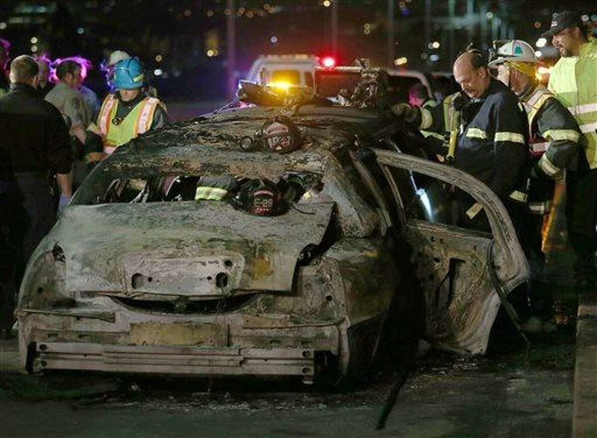 San Mateo County firefighters and California Highway Patrol personnel investigate the scene of a limousine fire on the westbound side of the San Mateo-Hayward Bridge in Foster City, Calif., on Saturday, May 4, 2013. Five people died when they were trapped in the limo that caught fire as they were traveling, and four others and the driver were able to escape, according to the Oakland Tribune-Bay Area News Group. (AP Photo/Oakland Tribune-Bay Area News Group, Jane Tyska)