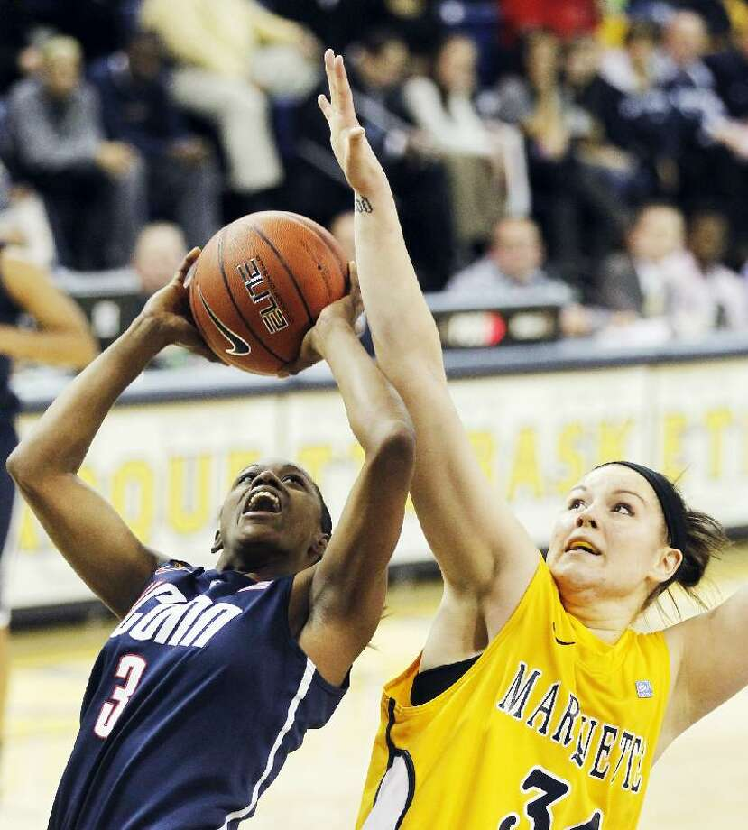 ASSOCIATED PRESS Connecticut's Tiffany Hayes (3) shoots against Marquette's Chelsie Butler, right, in the first half of Saturday's game in Milwaukee. The Huskies won the game 85-45.