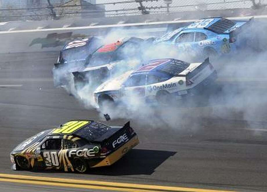 Elliott Sadler (2), Tony Stewart (33), Trevor Bayne (60), and Joey Logano (20) crash as James Buescher (30) drives past to win the NASCAR Drive4COPD 300 Nationwide series auto race in Daytona Beach, Fla., Saturday, Feb. 25, 2012. (AP Photo/Zack Hughes) Photo: ASSOCIATED PRESS / AP2012