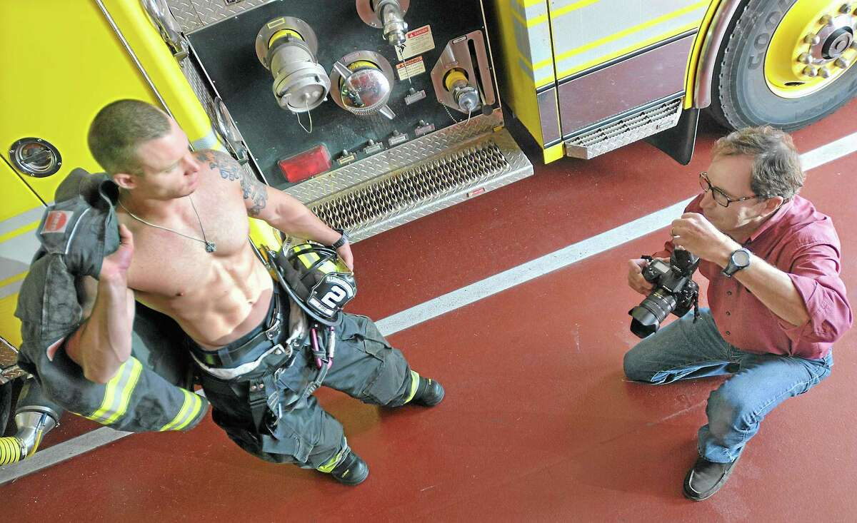 Commercial photographer John Giammatteo, of Middlefield, photographs firefighter Bill O'Donnell at the Cross Street Fire Station Monday afternoon. Giammatteo is volunteering his services to produce images of Middletown firefighters for the MARC: Community Resources fundraising 2014 calendar.