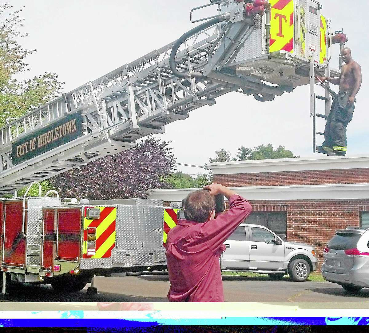Commercial photographer John Giammatteo photographs a firefighter at the Cross Street Fire Station Monday afternoon.