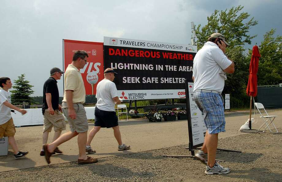Cromwell-- Spectators leave the Travelers Championship golf tournament after lightning storms stopped play in the mid-afternoon.  Peter Casolino/New Haven Register  06/22/2012
