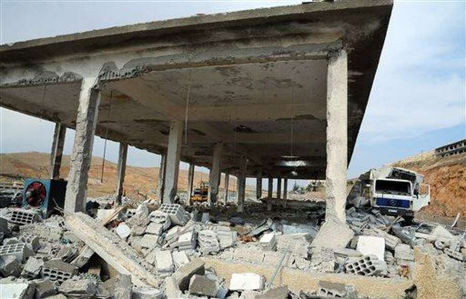 This photo released by the Syrian official news agency SANA shows a general view of damaged buildings wrecked by an Israeli airstrike, in Damascus, Syria, Sunday, May 5, 2013. Israeli warplanes struck areas in and around the Syrian capital early Sunday, setting off a series of explosions as they targeted a shipment of highly accurate, Iranian-made guided missiles believed to be on their way to Lebanon's Hezbollah militant group, officials and activists said. The attack, the second in three days, signaled a sharp escalation of Israel's involvement in Syria's bloody civil war. Syria's state media reported that Israeli missiles struck a military and scientific research center near the Syrian capital and caused casualties. (AP Photo/SANA) Photo: AP / SANA