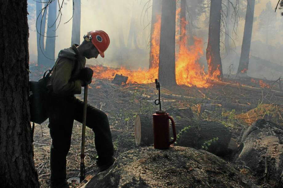 In this photo provided by the U.S. Forest Service, a Hotshot fire crew member rests near a controlled burn operation at Horseshoe Meadows, as crews continue to fight the Rim Fire near Yosemite National Park in California Wednesday, Sept. 4, 2013. The massive wildfire is now 80 percent contained according to a state fire spokesman. The Rim Fire's southeast flank in Yosemite National Park is expected to remain active where unburned fuels remain between containment lines and the fire. (AP Photo/U.S. Forest Service, Mike McMillan) Photo: AP / USFS