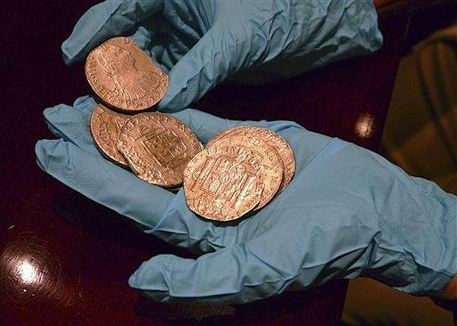 In this undated photo made available by the Spain's Culture Ministry, a member of the Ministry technical crew displays some of the 594,000 coins and other artifacts found in the Nuestra Senora de las Mercedes, a Spanish galleon sunk by British warships in the Atlantic while sailing back from South America in 1804, in a warehouse in Tampa, Fla. A 17-ton trove of silver coins recovered from the Spanish galleon was set to be flown Friday from the United States to Spain, concluding a nearly five-year legal struggle with Odyssey Marine Exploration, the Florida deep-sea explorers who found and recovered it.  Associated Press Photo: AP / Spanish Culture Ministry