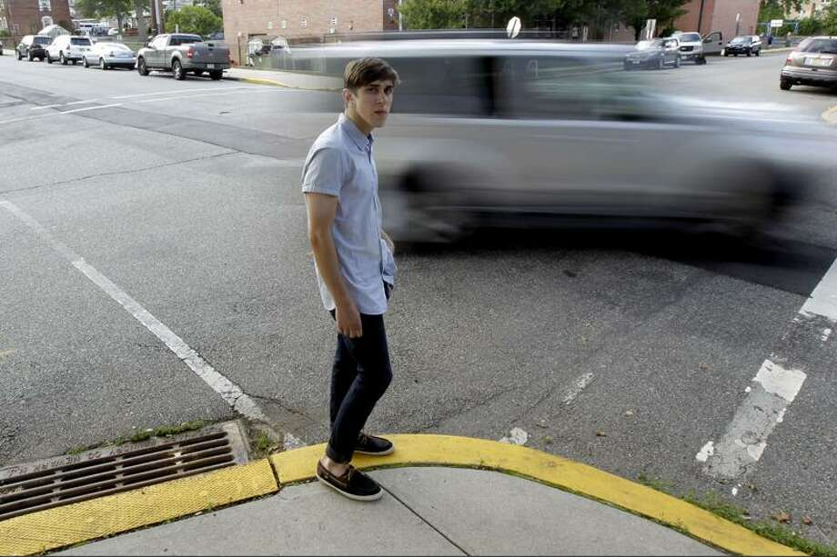 Dylan Young, 18, poses as a vehicle cruises by, June 6, 2012, in North Arlington, N.J. Young, a senior at North Arlington High, was in a fender-bender accident caused by being distracted while texting and driving. (Julio Cortez/AP Photo) Photo: AP / AP