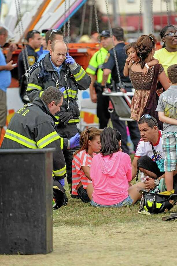 Thirteen children were injured when a festival attraction that swings riders into the air lost power at a community fair in Norwalk, Conn, on Sunday Sept. 8, 2013,  but none of the injuries appeared to be life-threatening, authorities said. Most of the children suffered minor injuries and were treated at the Oyster Festival in Norwalk, police said. Norwalk Police Chief Thomas Kulhawik said there were initial reports of serious injuries but preliminary indications are that the injuries were not as severe as first feared.  (AP Photo/The Hour Miguel Cruz) MANDATORY CREDIT Photo: AP / The Hour
