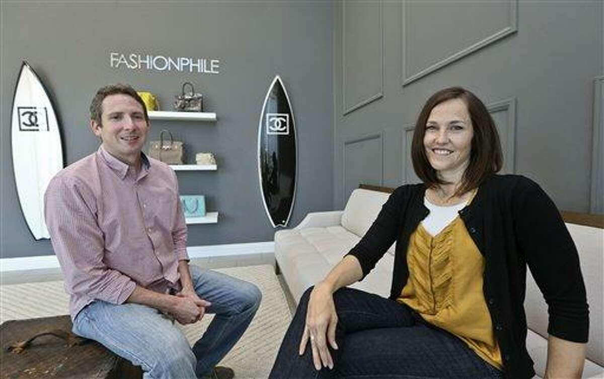 This photo taken May 2, 2013, shows Sarah Davis and Ben Hemmnger, co-owners of Fashionphile.com, posing in the lobby of their Carlsbad, Calif. office. The Internet company sells rare, vintage, and discontinued previous owned bags and is facing the complicated task of dealing with new state regulations on Internet sale taxes. (AP photo/Lenny Ignelzi)