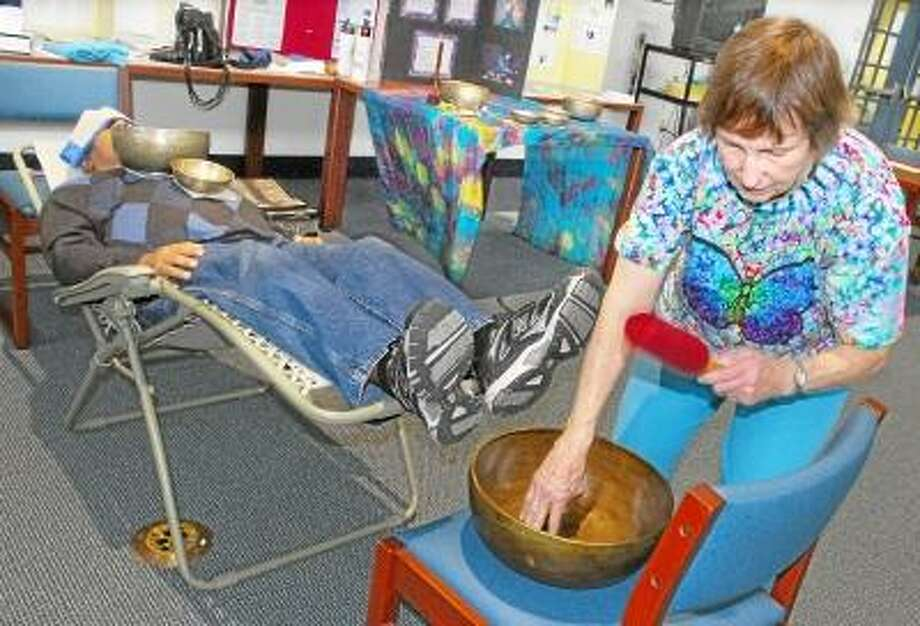 """CATHERINE AVALONE/THE MIDDLETOWN PRESS Marie Menut, R.N., a vibrational healer from East Hartford, uses Tibetan singing bowls on staff and patients attending the Connecticut Valley Hospital Health Fair. The singing bowls create a sound that is believed to improve physical, spiritual and emotional being. """"Each metal vibrates at its own rate,"""" Menut said, """"and cells of our body relax to the vibration and react to the optimum rate."""""""