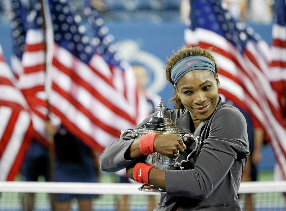 Serena Williams hugs the championship trophy after defeating Victoria Azarenka during the women's final of the U.S. Open on Sunday.