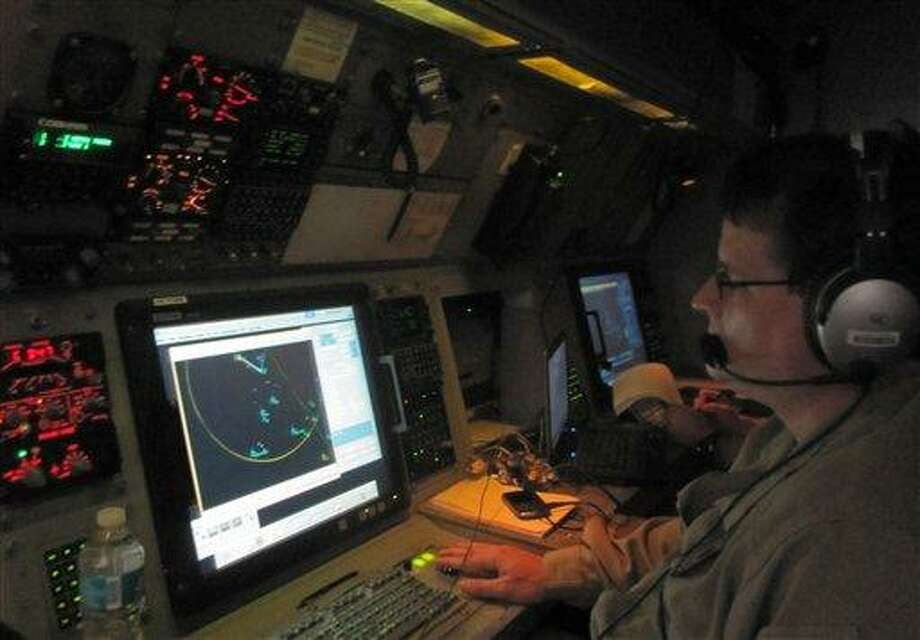 In this Jan. 25, 2013 photo, a U.S. Customs and Border Protection detection officer analyzes radar signals inside a P3 Orion Airborne Early Warning Aircraft while flying over waters near the Pacific coast of Costa Rica.The Central American country abolished its army in 1948 and plowed money into education, social benefits and environmental preservation. As a result, Costa Rican officials say, the country can't battle ruthless and well-equipped Mexican drug cartels without U.S. help. The U.S. is patrolling Costa Rica's skies and waters and providing millions of dollars in training and equipment to Costa Rican officials who have launched a tough line on crime backed by top-to-bottom transformation of the law-enforcement and justice systems. (AP Photo/Mike Weissenstein) Photo: AP / AP