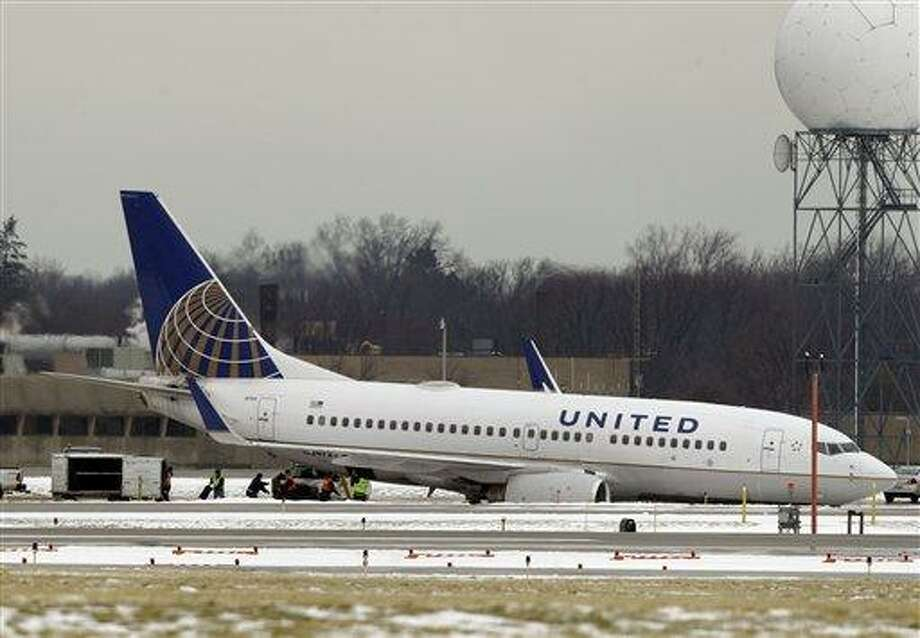 Workers remove luggage from a United Airlines jet that slid off a taxiway at Cleveland Hopkins International airport Friday, Feb. 22, 2013. No injuries were reported for any of the 103 passengers and five crew members on flight 1639 from Ft. Lauderdale, Fla. (AP Photo/Mark Duncan) Photo: AP / AP