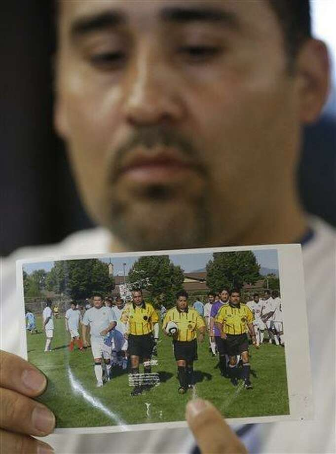 Jose Lopez, points to a undated photo of Riccardo Portillo, center, his brother-in-law, following a news conference Thursday, May 2, 2013, at Intermountain Medical Center, in Murray, Utah. A longtime Utah soccer referee is in a coma after being punched by a teenage player unhappy with one of his calls during a weekend game, and his family says they're hoping for the man's miraculous recovery and want justice for him. Ricardo Portillo, 46, has swelling in his brain and his recovery is uncertain as he remains in critical condition, Dr. Shawn Smith said Thursday at the Intermountain Medical Center in the Salt Lake City suburb of Murray. Police say a 17-year-old player in a recreational soccer league punched Portillo after the man called a foul on him and issued him a yellow card. The teen has been booked into juvenile detention on suspicion of aggravated assault. Those charges could be amplified if Portillo dies. (AP Photo/Rick Bowmer) Photo: AP / AP