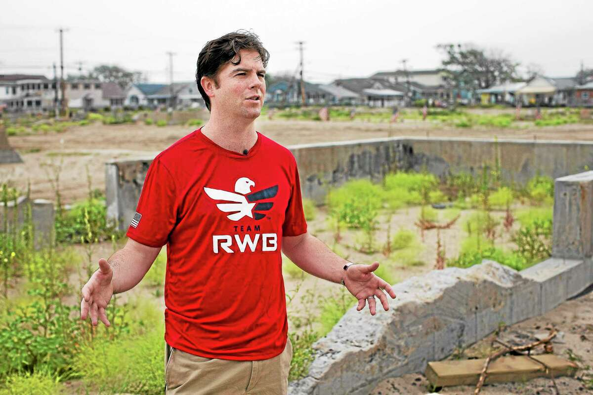 In this Sept. 2 2013, photo, Joe Quinn speaks to a reporter next to the remains of his parents' home that was destroyed by Superstorm Sandy in the Breezy Point neighborhood of New York's Queens borough.