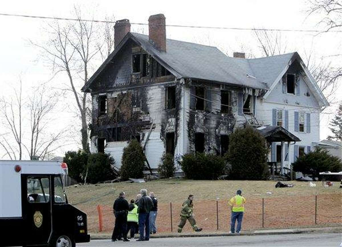Emergency personnel work around the scene of a fatal fire in South Plainfield, N.J., Thursday. A fast-burning fire destroyed half of the duplex home early Thursday, killing five members of a family and injuring four others, authorities said. Relatives and neighbors said the dead included several children. Associated Press