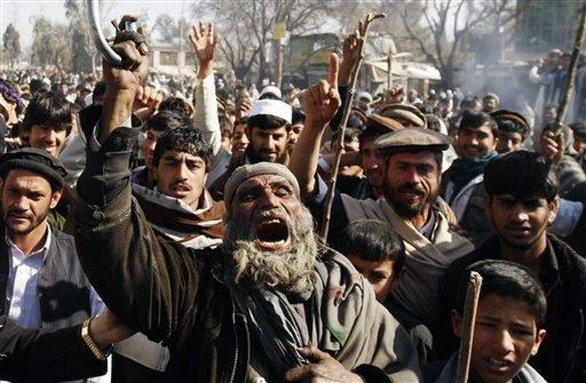 Afghans shout anti-U.S. slogans during a demonstration in Mehterlam, Laghman province east of Kabul, Afghanistan, Thursday. Afghan police on Thursday fired shots in the air to disperse hundreds of protesters who tried to break into an American military base in the country's east to vent their anger over this week's Quran burnings incident. Associated Press