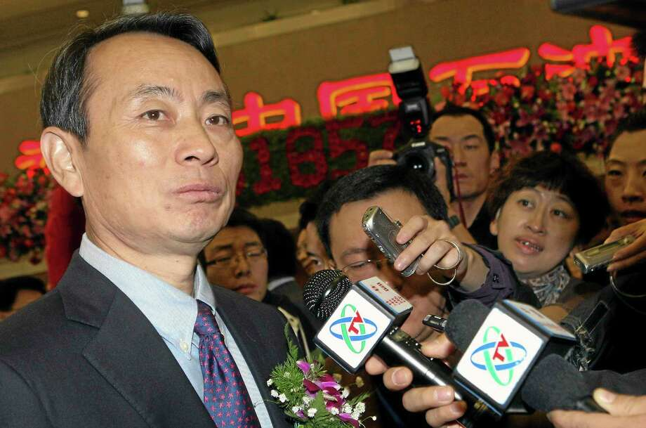 Jiang Jiemin, chairman of PetroChina, left, is mobbed by journalists after attending an IPO ceremony for PetroChina at the Shanghai Stock Exchange in Shanghai. Chinese authorities announced an investigation into the head of a commission that oversees China's state-owned companies in the country's latest high-profile corruption case. Photo: Photo By The Associated Press  / CHINATOPIX