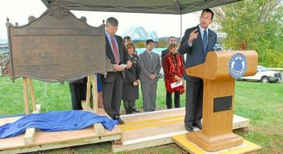 CATHERINE AVALONE/THE MIDDLETOWN PRESS  Governor Dannel P. Malloy and James Redeker, Commissioner of the State Department of Transportation, at left, joined Congresswoman Rosa DeLauro, Middletown Mayor Dan Drew, and Portland First Selectwoman Susan Bransfield celebrated the completion of the year-long rehabilitation of the Arrigoni Bridge. Officials unveiled the original 1938 bronze bridge marker during the rededication ceremony.