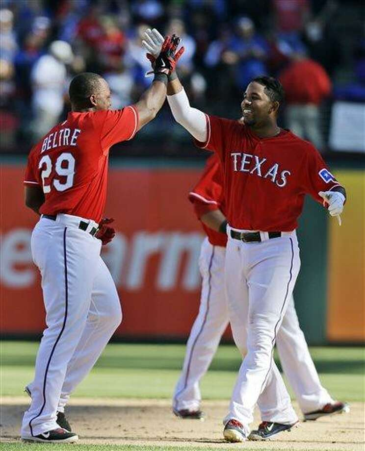 Texas Rangers' Adrian Beltre, left, celebrates with Elvis Andrus after Beltre's winning RBI single scored Andrus in the ninth inning of a baseball game against the Boston Red Sox, Sunday, May 5, 2013, in Arlington, Texas. The Rangers won 4-3. (AP Photo/LM Otero) Photo: AP / AP