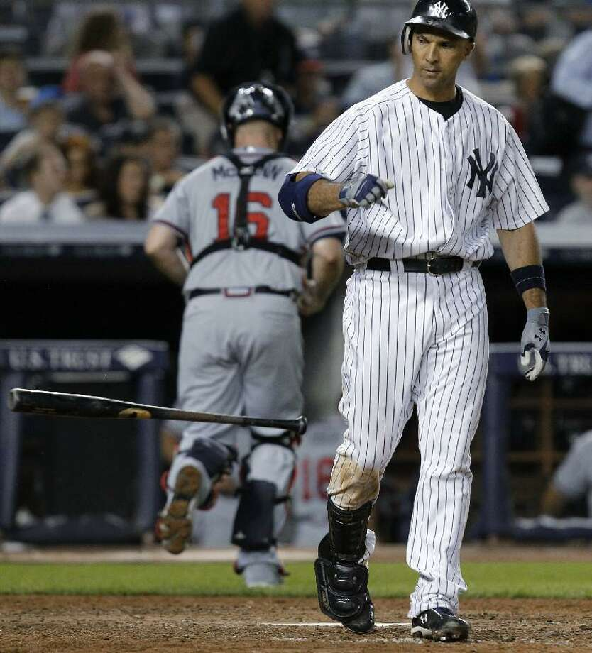ASSOCIATED PRESS New York Yankees Raul Ibanez tosses his bat after a seventh-inning strikeout as Atlanta Braves catcher Brian McCann returns to the dugout during Tuesday night's game at Yankee Stadium in New York. The Yankees lost 4-3. Ibanez stranded two runners on base on his strikeout.