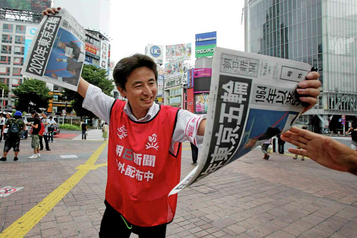 A vendor hands out free copies of a newspaper special edition printed to mark the announcement of Tokyo as the host of the 2020 Olympic Games. The headline reads: 2020 Tokyo Olympics, 56 years since the 1964 Tokyo Olympics.