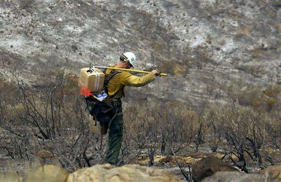 A firefighter carries tools down a burned hill after a wildfire in Point Mugu on Friday, May 3, 2013. A huge wildfire carved a path to the sea and burned on the beach Friday, but firefighters got a break as gusty winds turned into breezes. Temperatures remained high, but humidity levels were expected to soar as cool air moved in from the ocean and the Santa Ana winds retreated. (AP Photo/Nick Ut) Photo: AP / AP