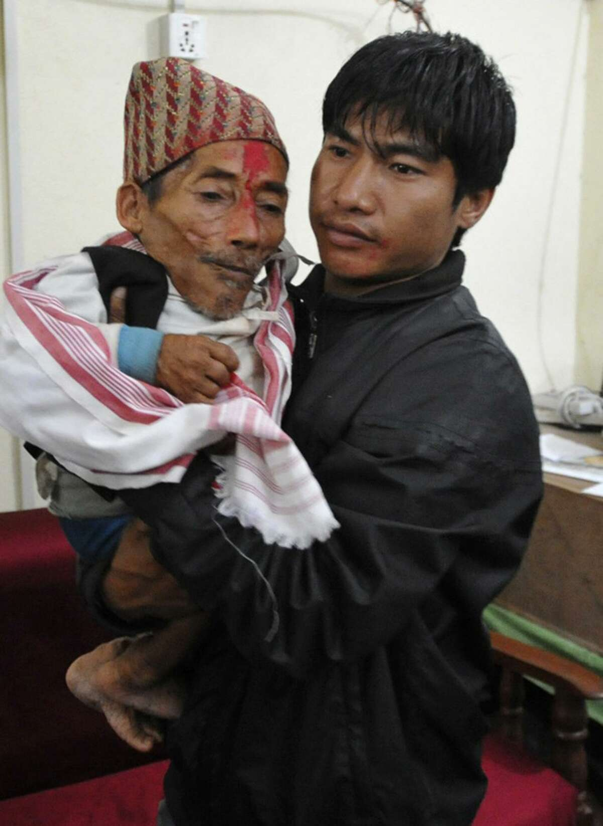 A relative carries Nepalese Chandra Bahadur Dangi, 72, who claims to be only 22 inches tall, in Nepalgunj, Nepal, Tuesday. Dangi is hoping to prove to Guinness World Records that he's the world's shortest man. Guinness World Records currently recognizes Junrey Balawing of the Philippines, who is 23.5 inches tall, as the shortest man in the world. (AP Photo/Subrot Neupane)