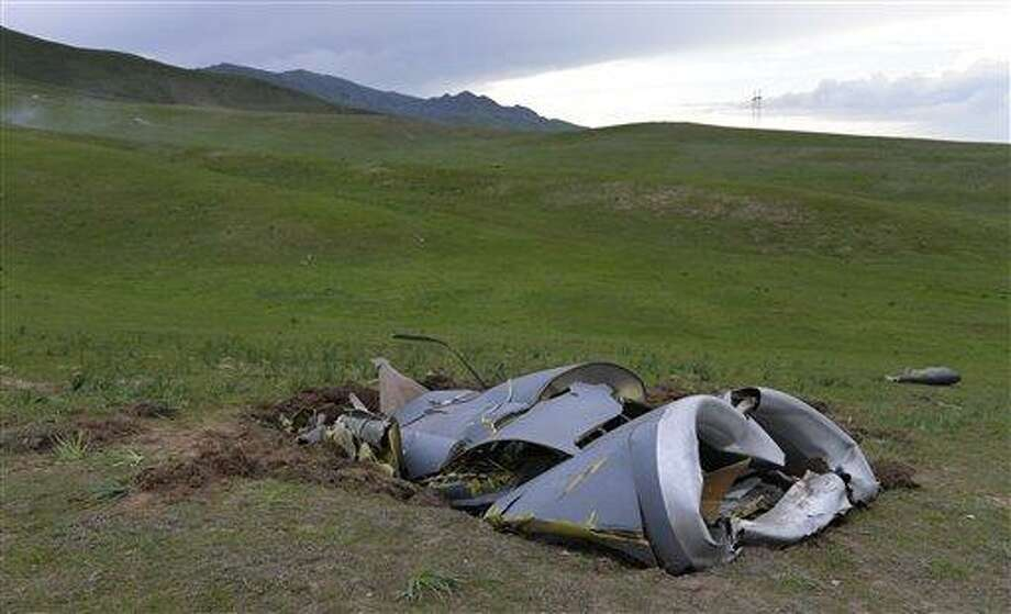 Wreckage from a U.S. Air Force KC-135 tanker aircraft wreckage is strewn across a field near the village of Chaldovar, about 100 miles (160 kms) west of the Kyrgyz capital Bishkek, Friday, May 3, 2013. The emergencies ministry in Kyrgyzstan says a US military plane has crashed in the country. Kyrgyzstan hosts a US base that is used for troops transiting into and out of Afghanistan and for C-135 tanker planes that refuel warplanes in flight. (AP Photo/Vladimir Voronin) Photo: AP / AP