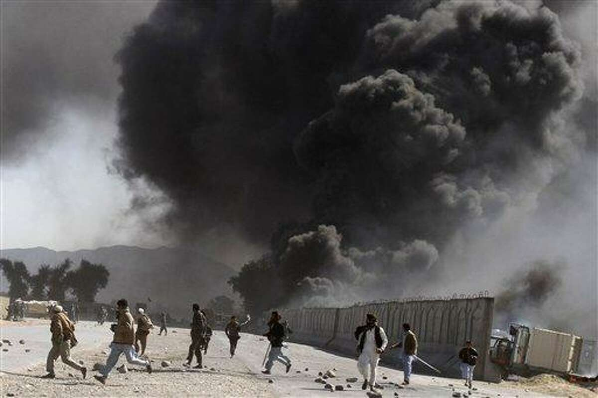 Protesters run as smoke raises from a burning truck during an anti-US demonstration at a NATO military base in Jalalabad, east of Kabul, Afghanistan, Wednesday. Associated Press