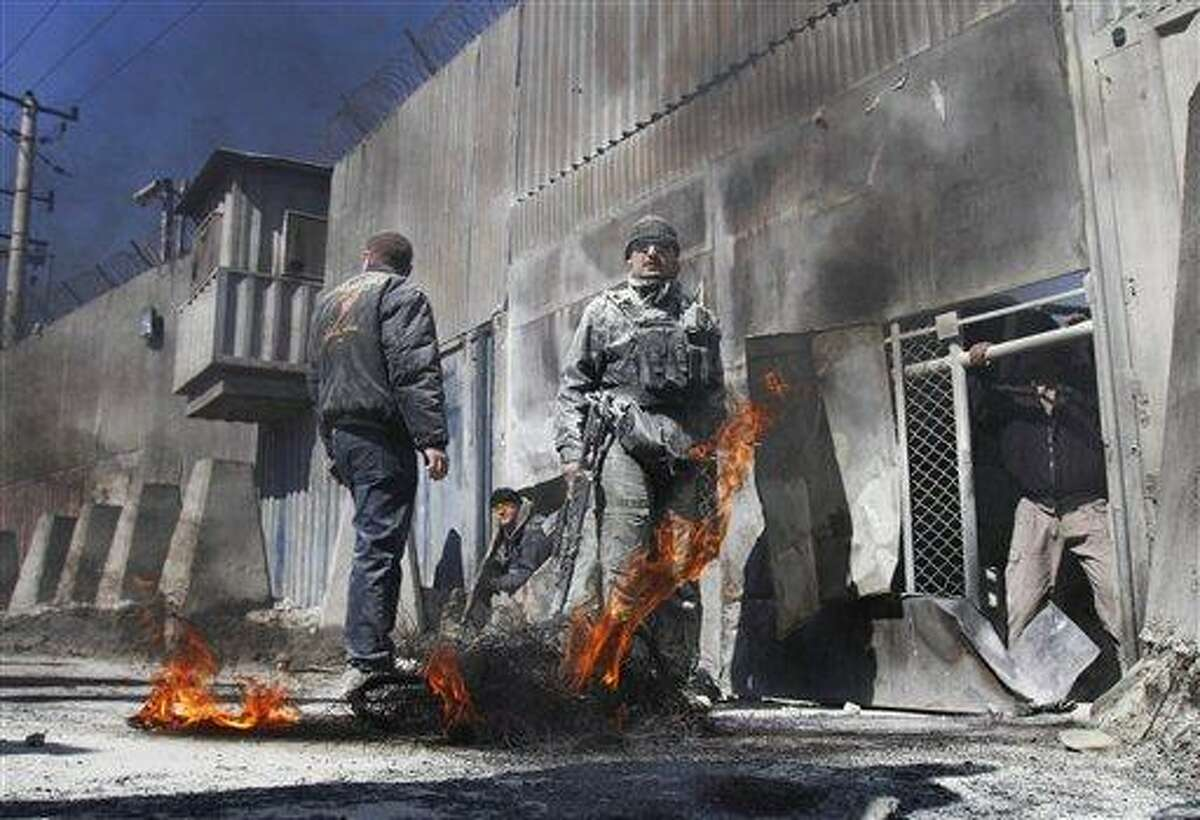 Security guards stand as black smoke rises from tyres which were burnt by protesters during an anti-US demonstration in Kabul, Afghanistan, Wednesday. Associated Press