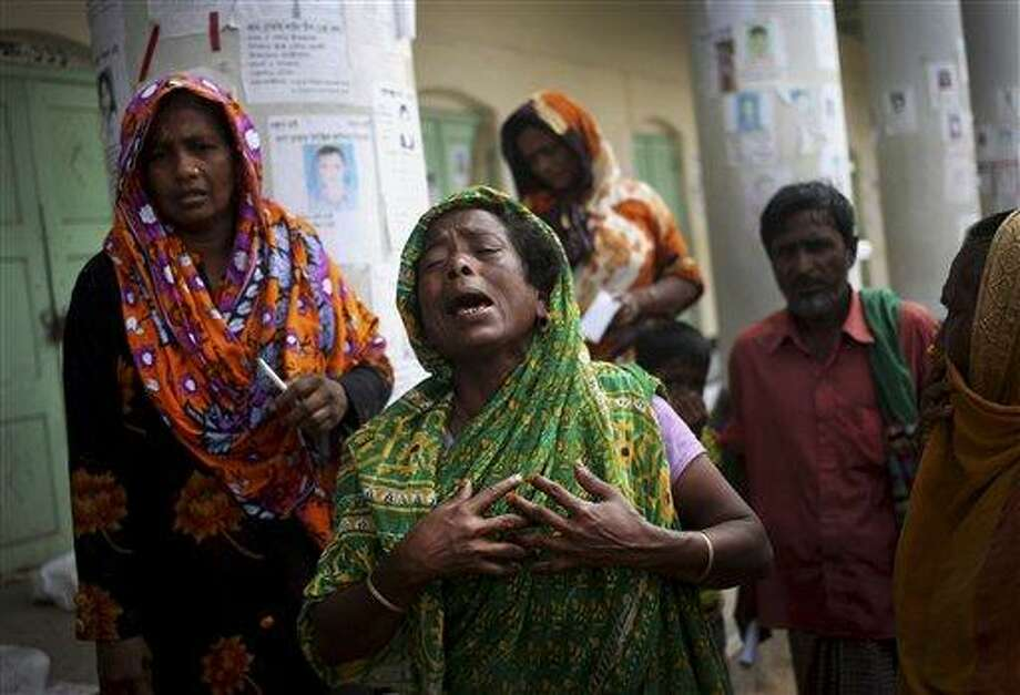 A woman grieves for her late relative after his body was pulled from the rubble in the collapsed garment factory building and brought to the morgue, in Savar, near Dhaka, Bangladesh, Saturday, May 4, 2013. In the aftermath of a building collapse that killed more than 530 people, Bangladesh's garment manufacturers may face a choice of reform or perish. (AP Photo/Wong Maye-E) Photo: AP / AP