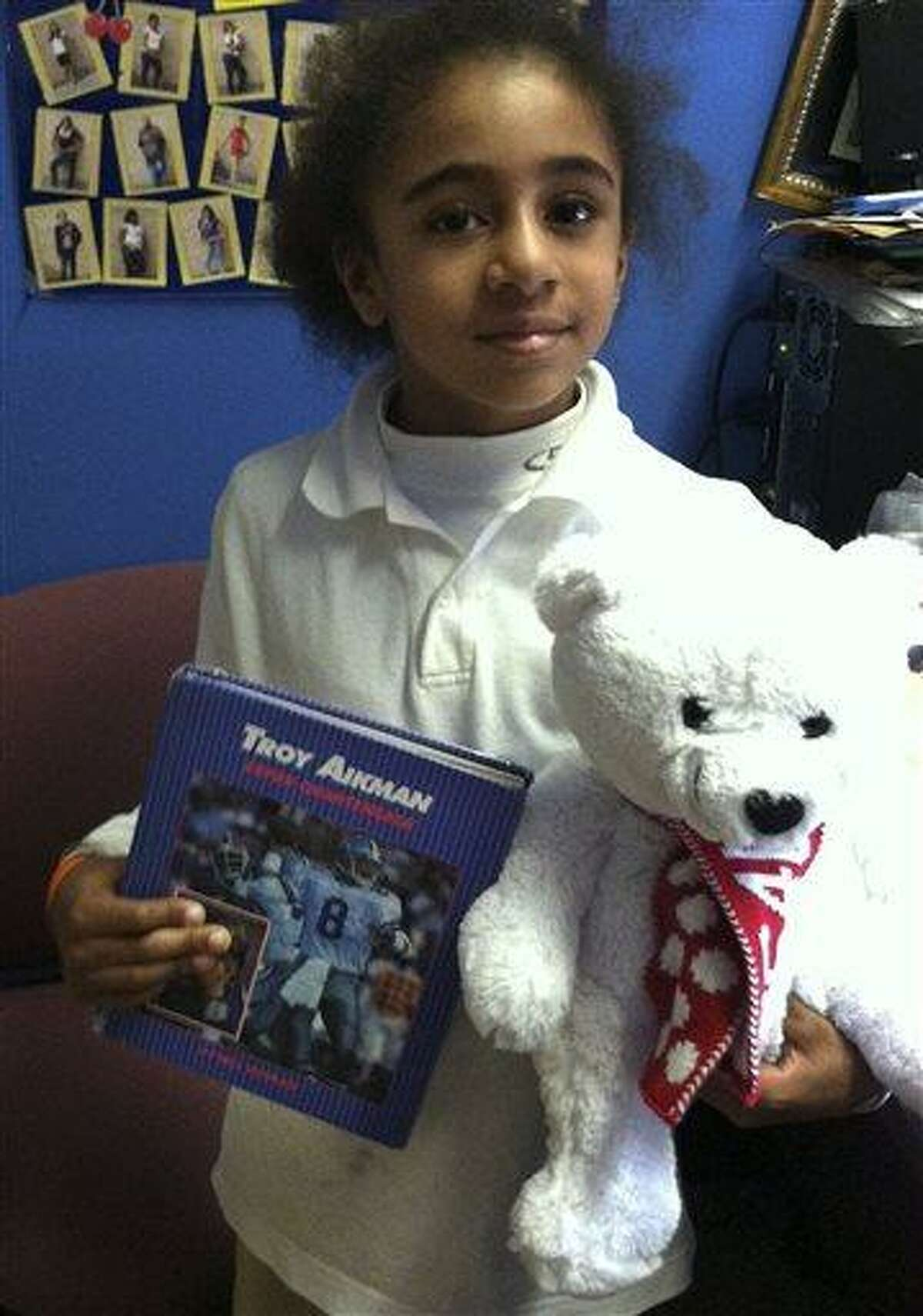 In this photo provided Monday, April 8, 2013 by R.E.A.L. Skills Network in Poughkeepsie, N.Y., Rashid Ricketts, 9, poses with some items the group received which originally had been donated to Newtown, Conn., after the December Sandy Hook Elementary School shooting. Newtown officials and families of those killed gave away 63,790 stuffed animals and thousands of other gifts that poured into the town in the weeks following the massacre. The final boxes of toys and school supplies were shipped out of the warehouse on March 29, 2013. (AP Photo/R.E.A.L. Skills Network)