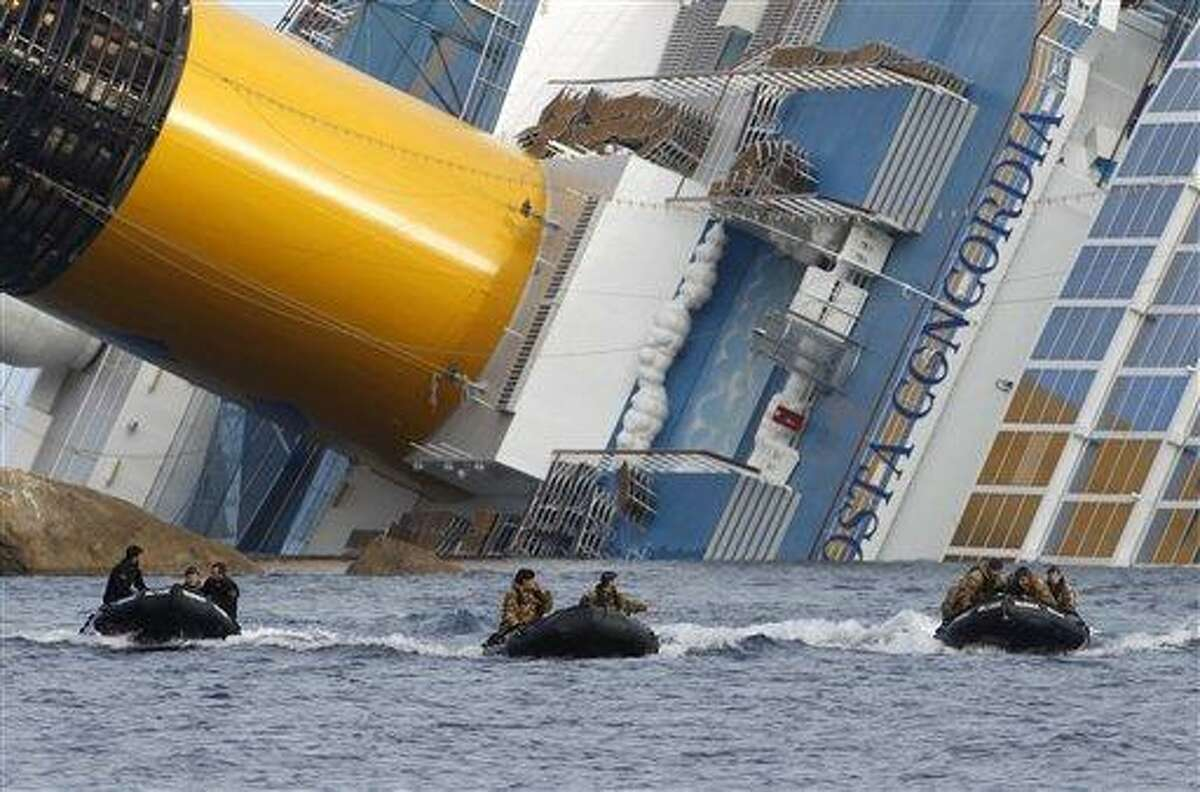 Divers return after working on the grounded cruise ship Costa Concordia Jan. 23 off the Tuscan island of Giglio, Italy. Divers searching the capsized Costa Concordia cruise ship found four more bodies Wednesday including that of a missing 5-year-old Italian girl, authorities said. Associated Press