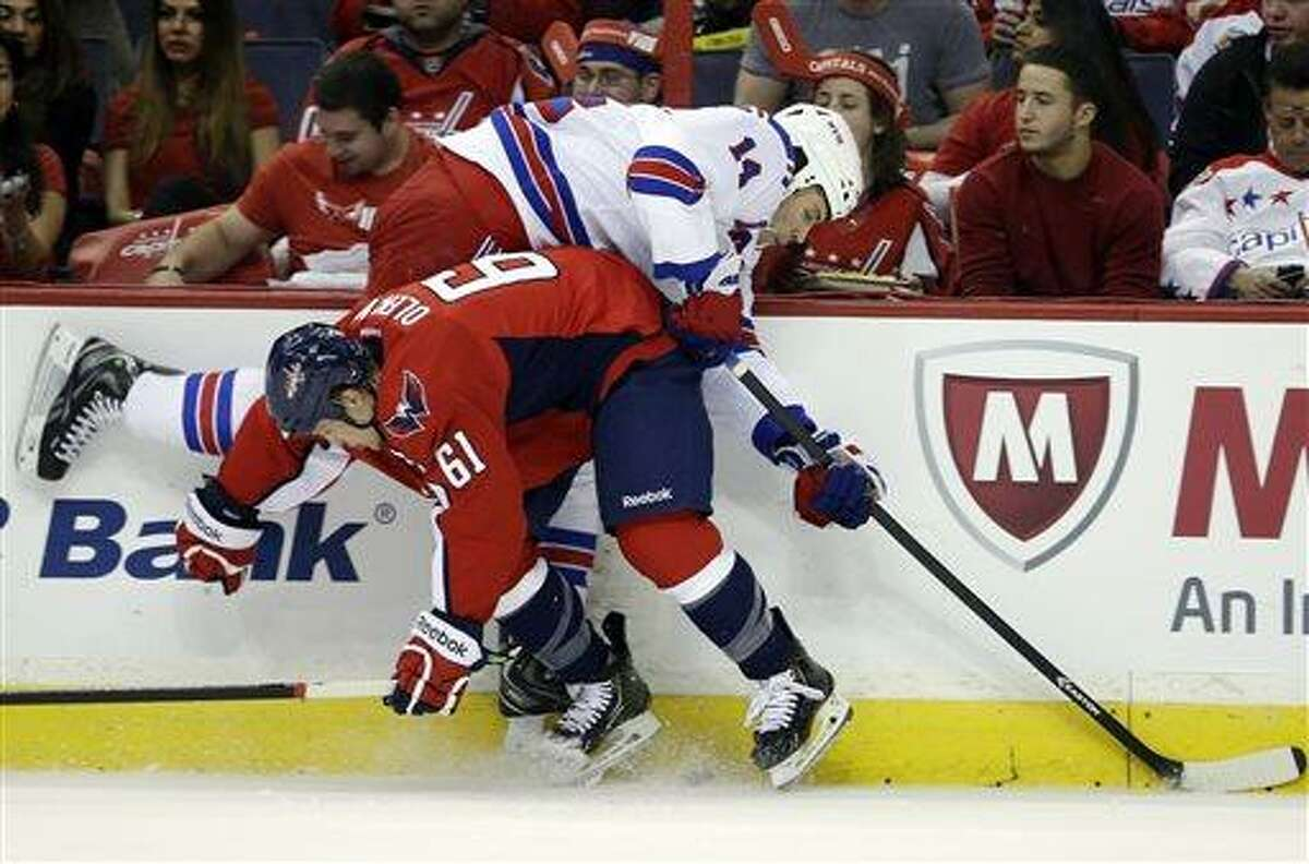 Washington Capitals defenseman Steven Oleksy (61) checks New York Rangers left wing Taylor Pyatt (14) during the second period in Game 2 of an NHL hockey Stanley Cup first-round playoff series, Saturday, May 4, 2013, in Washington. (AP Photo/Evan Vucci)