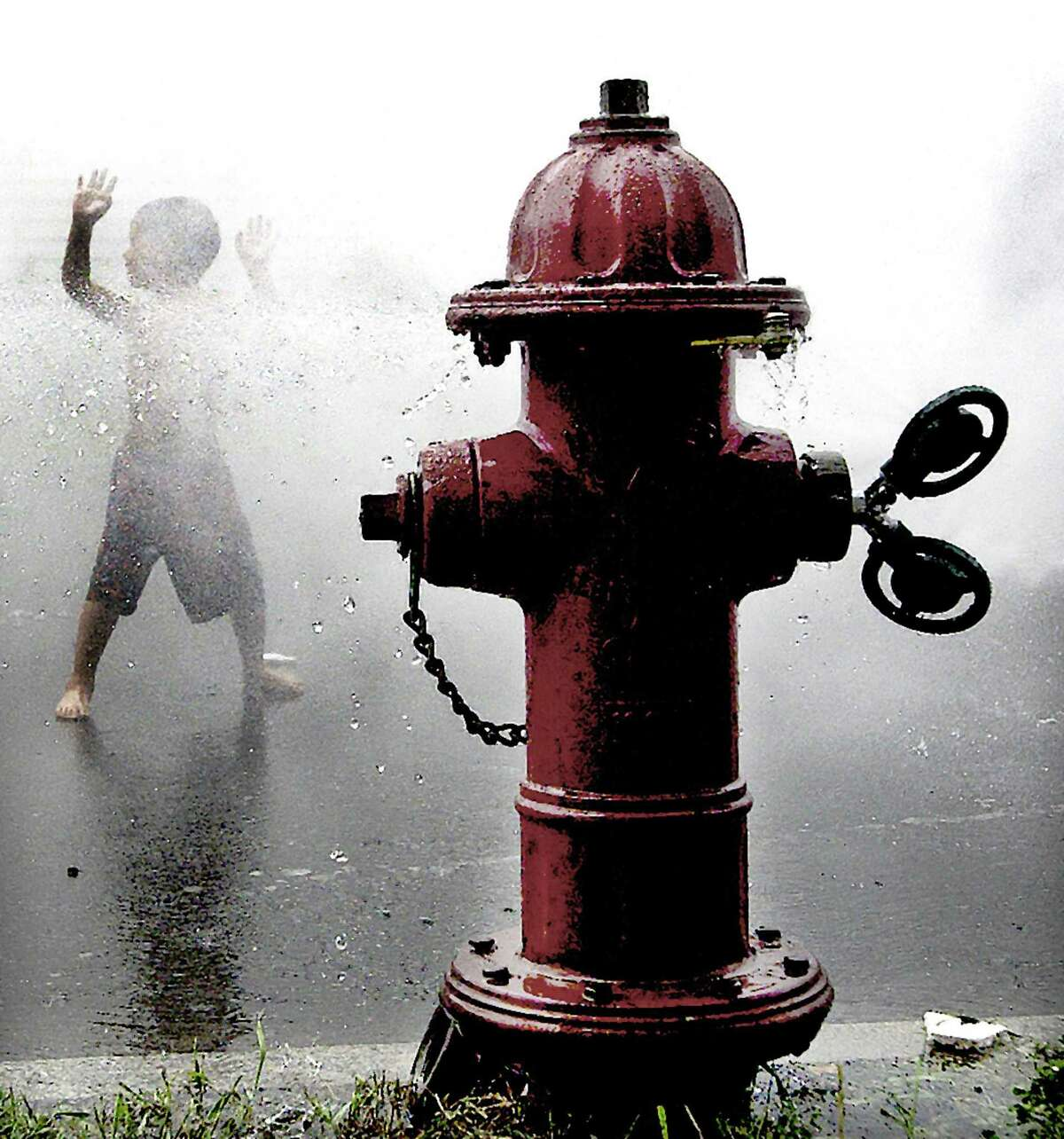 Hayd'n Santiago,4,, of Middletown, keeps cool running around the fire hydrant on Portland Street in Middletown in 2007. Catherine Avalone/The Middletown 7.11.07