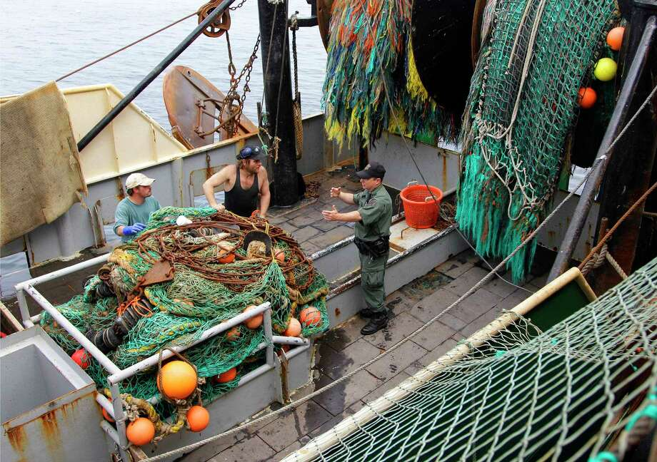 FILE - This May 14, 2012 file photo shows a Massachusetts Environmental Agency enforcement officer talking to members of the crew on the fishing vessel Green Acres in New Bedford, Mass. Federal efforts to rebuild depleted fish populations have largely been successful, but pressure to overfish some species remains high and some fish stocks have not rebounded as quickly as projected, a new report says The report comes from the National Research Council, an arm of the National Academies of Science. It says 43 percent of fish stocks identified as being overfished were rebuilt or showed good progress toward rebuilding within 10 years. Another 31 percent were on track to rebuild if sharply reduced fishing levels remain in place. But the report also says 26 percent of overfished stocks continue to be overfished. (AP Photo/Stephan Savoia, File) Photo: AP / AP
